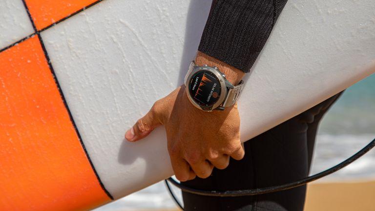 Surfer holding his board and wearing a Garmin Quatix 6X Solar outdoor watch