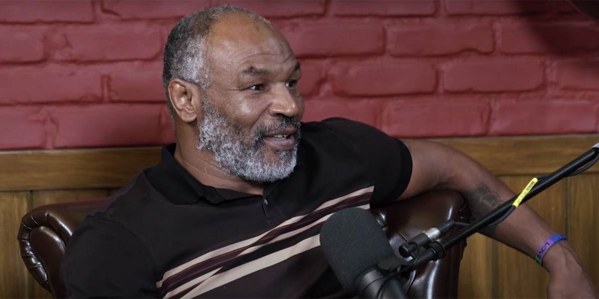 Mike Tyson wearing a black shirt and talking into a microphone while recording his podcast.