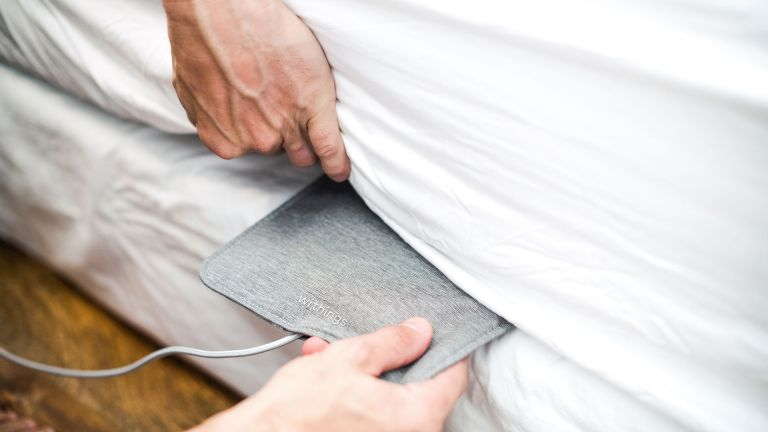 Withings Sleep Analyzer Mat being placed under a mattress