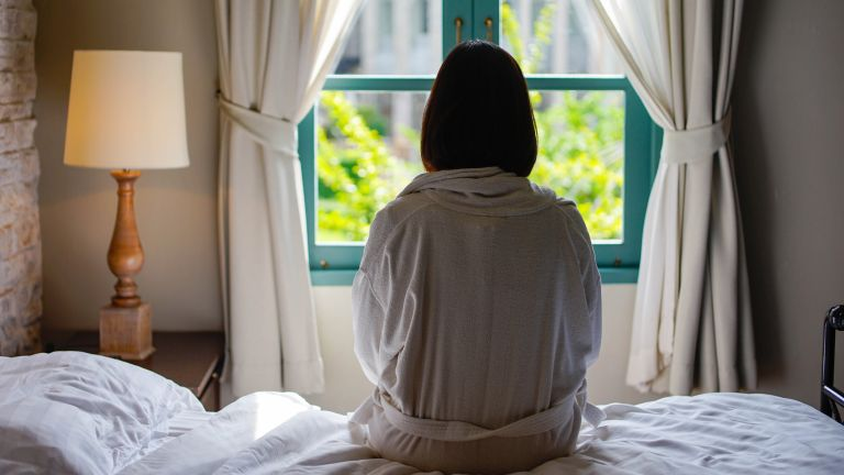 Woman sat on bed looking out window