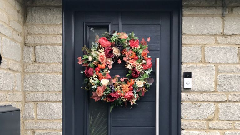 autumn wreath on a front door with red leaves and berries