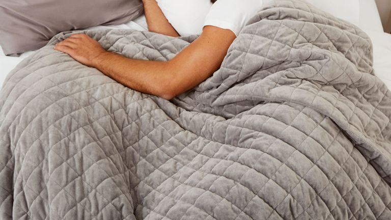 how to wash a weighted blanket - a man in bed with weighted blanket - mela