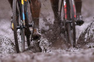 Cyclo-cross racers ride through muddy conditions