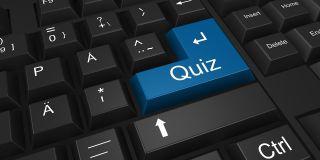 "Black computer keyboard with large ""Quiz"" key."