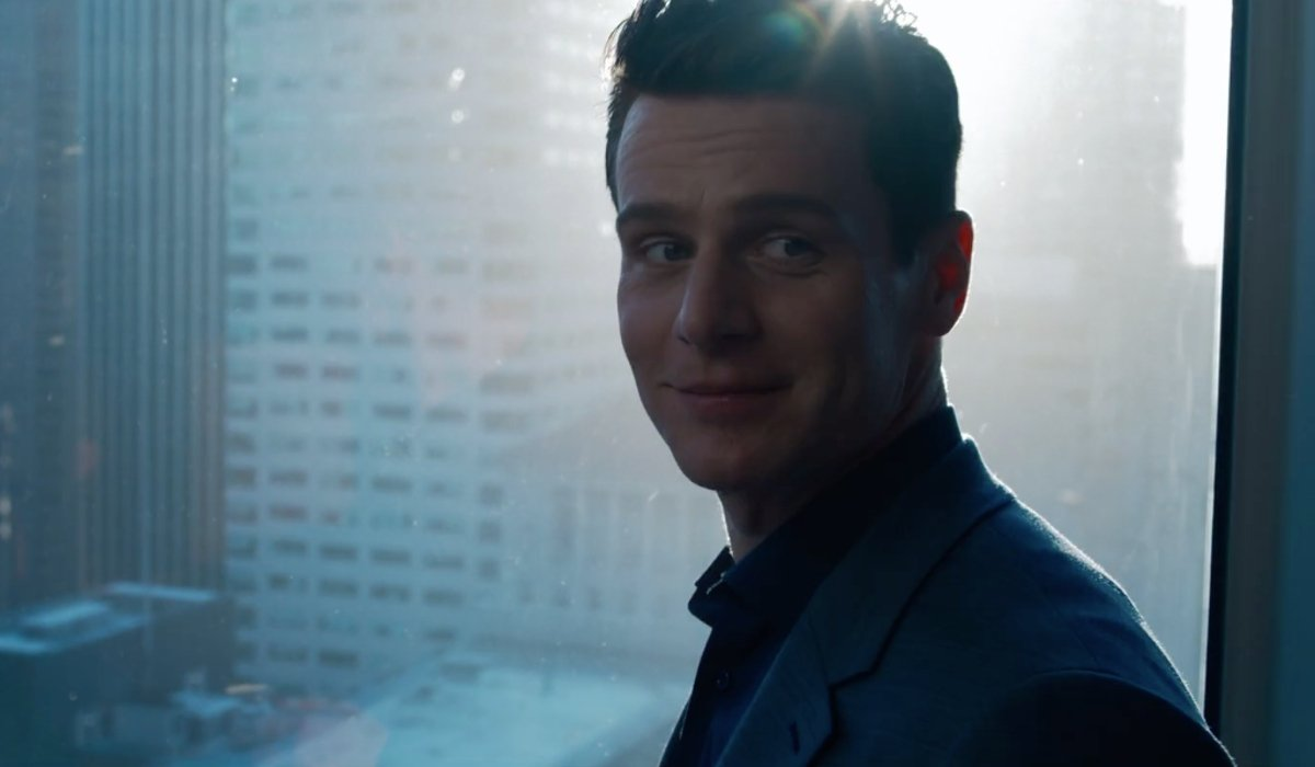Jonathan Groff looking back with a smile from his office window in The Matrix Resurrections.
