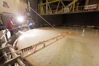 Technicians work on the mirror segment No. 2 for the Giant Magellan Telescope at the University of Arizona's Richard F. Caris Mirror Lab.