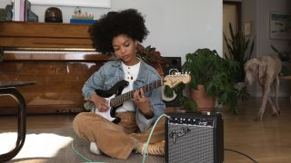 Person playing a Fender guitar