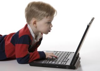 A young boy types on a computer.