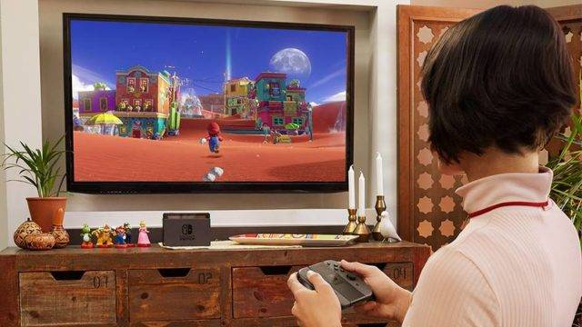 Woman playing Super Mario Odyssey on a Nintendo Switch in TV mode