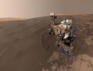 This recent self-portrait from NASA's Curiosity rover shows the robot shortly after it retrieved a sample of dark sand from shifting dunes along the flank of a Martian hillside.