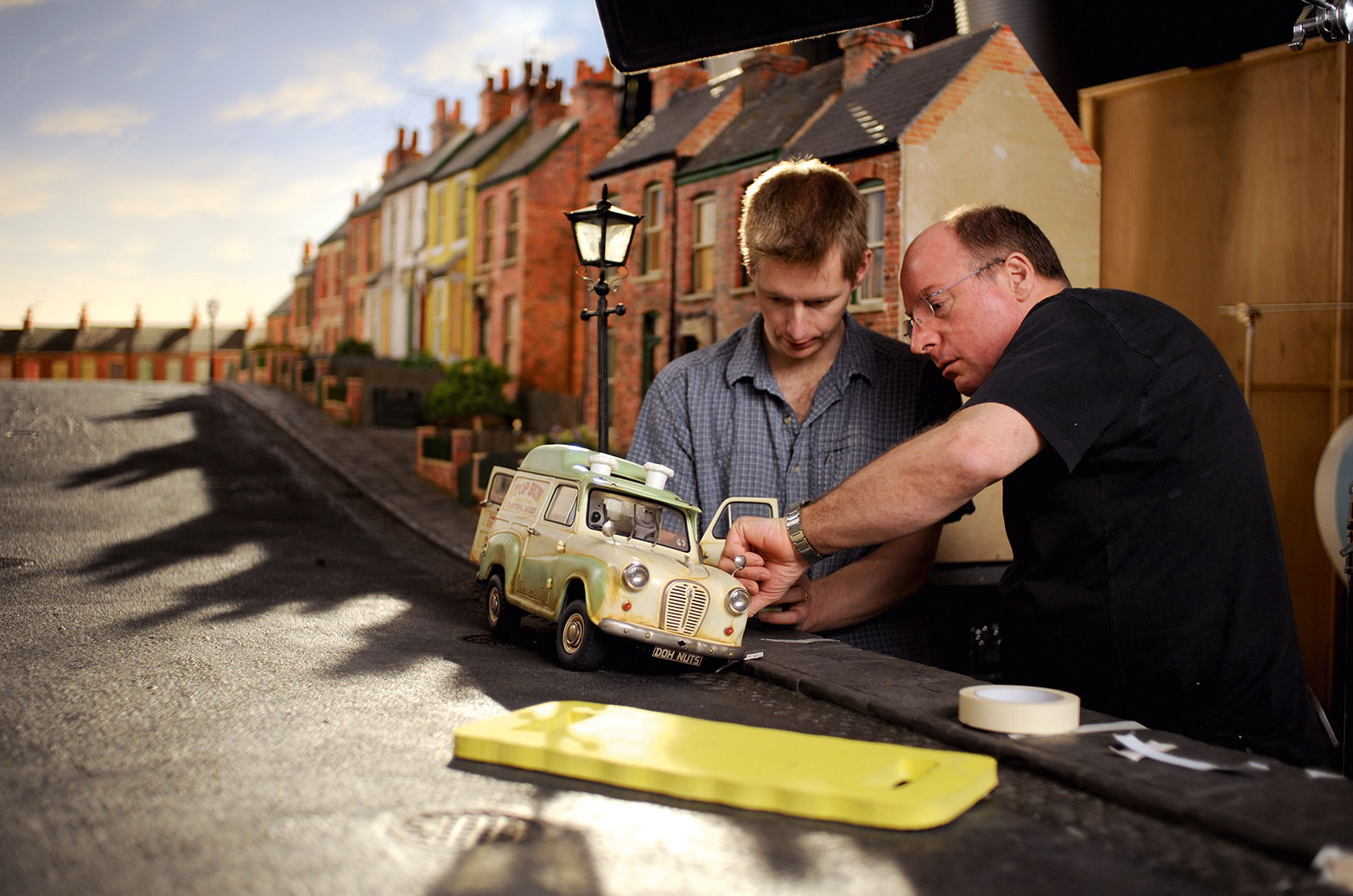 Two workers building a model van on a model road