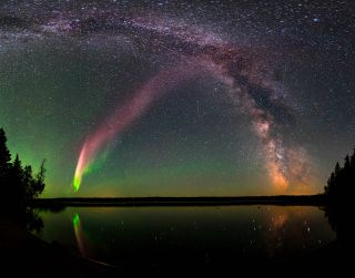 STEVE is visible as a pink band rising from the lower left to the upper right of the image, as seen with the Milky Way over Childs Lake in Manitoba, Canada.
