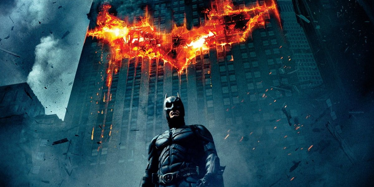 The Dark Knight Batman stands in front of a burning Batsymbol