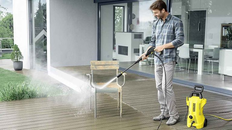 Kärcher K2 Full Control pressure washer in use in garden by man cleaning furniture