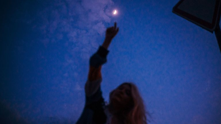 Young woman touching the moon on the dusk sky background