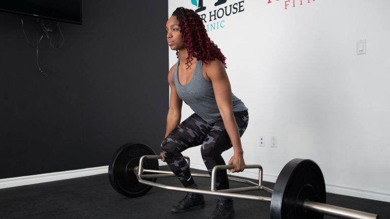 Woman doing a deadlift with a trap bar