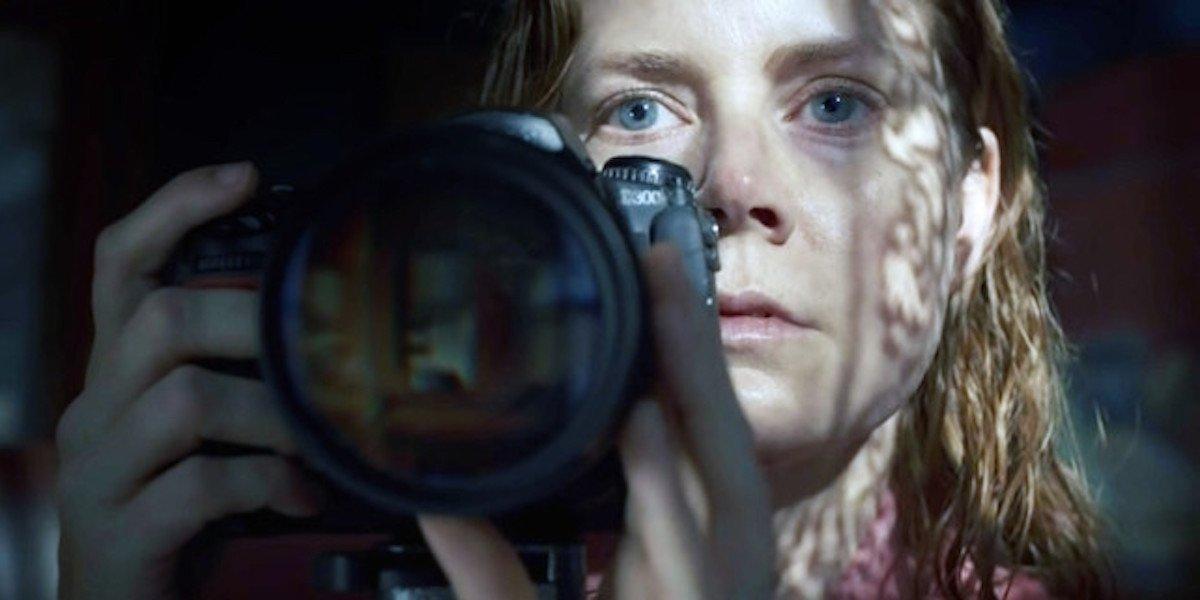 Amy Adams holding a camera in Rear Window