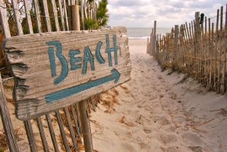 A wooden sign points the way to a beach.