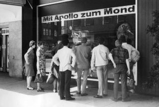 People in front of a TV shop in Germany watch the launch