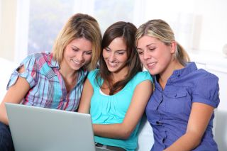 Three women look at a computer screen