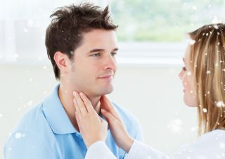 A doctor palpates a man's throat