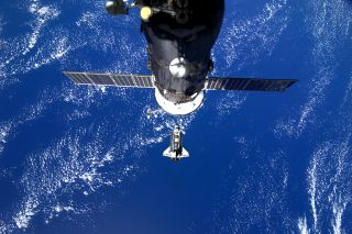 Space shuttle Discovery is seen pulling up to the International Space Station on Feb. 26, 2010 during docking day for its final space mission STS-133. Italian astroanut Paolo Nespoli took this photo from inside the station. A Russian spacecraft is visible