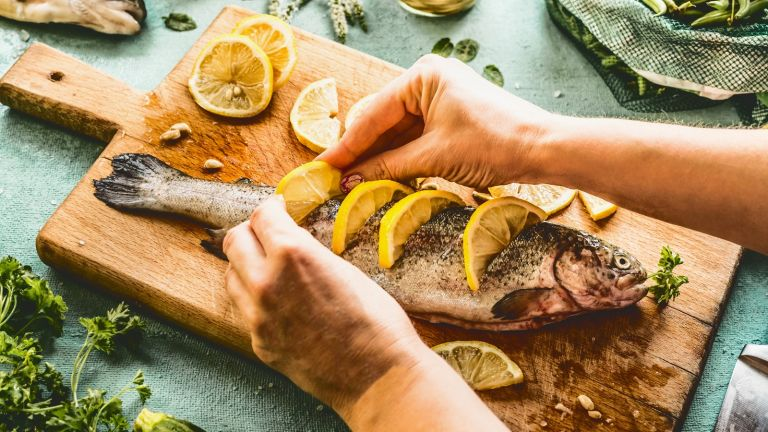 Woman preparing an oily fish dish with slices of lemon