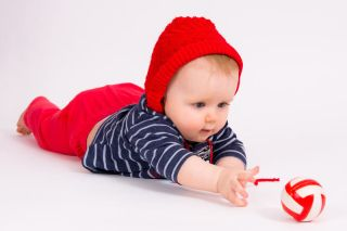 young baby playing with a red ball