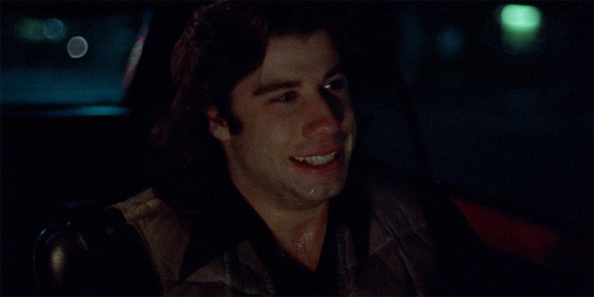 John Travolta as Billy Nolan driving a car in Carrie