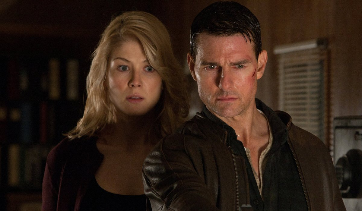 Tom Cruise holds someone at gunpoint while Rosamund Pike watches in Jack Reacher.