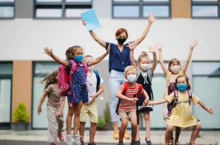 Kids in masks jump up and down with teacher