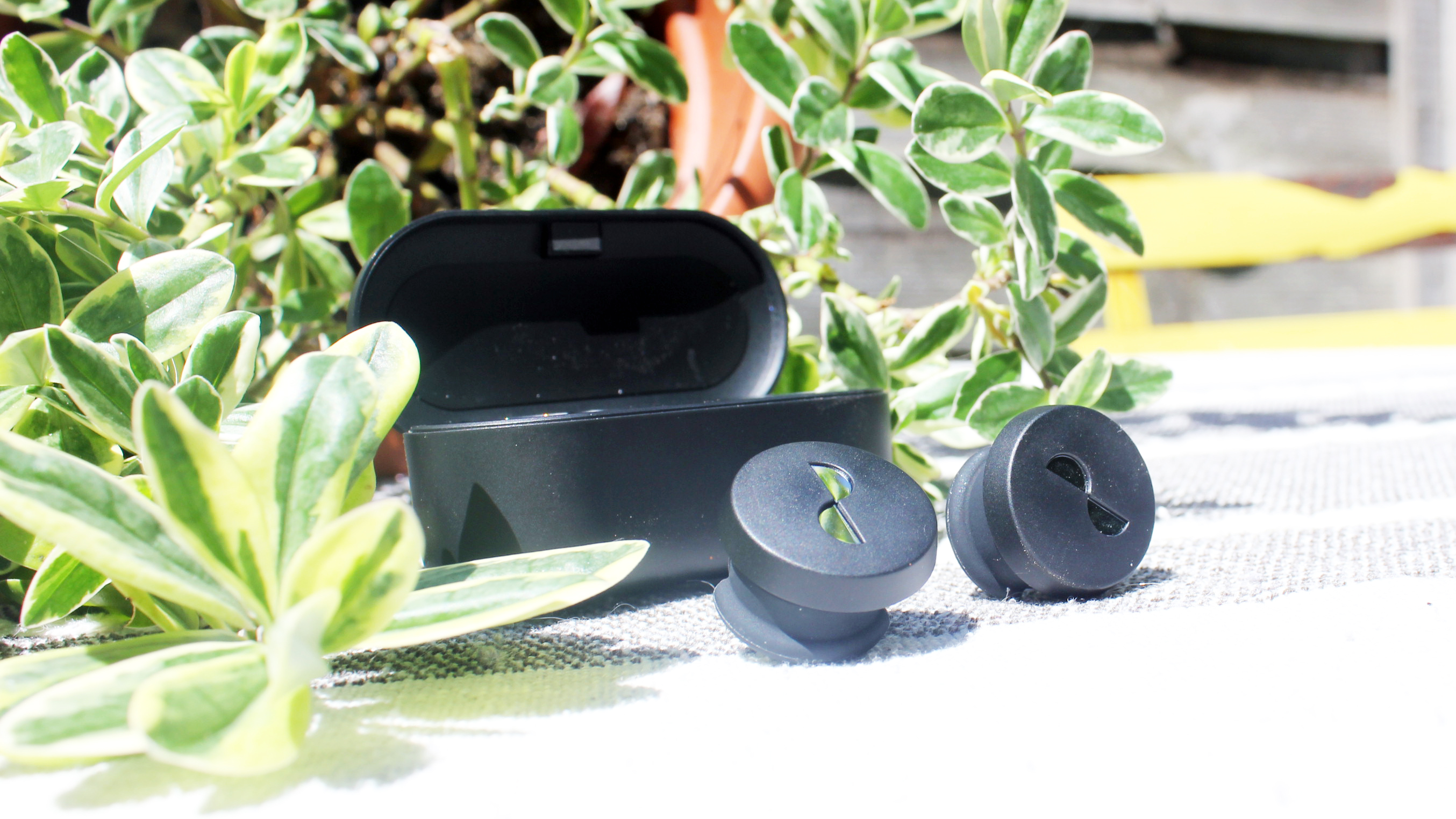 the nuratrue earbuds in front of their charging case
