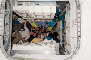 The crews of the International Space Station (Expedition 26) and the shuttle Discovery (STS-133) pose for a photo inside the newly attached Leonardo storage module, known as the Permanent Multipurpose Module, on March 1, 2011.