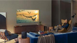 En man kollar på TV med en Samsung HW-Q950a soundbar