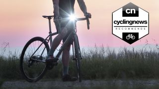Best StVZO bike lights: a cyclist in front of a sunrise with a bright front light