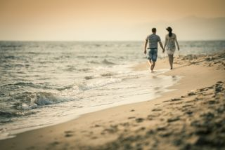 Romantic couple walking on the beach.