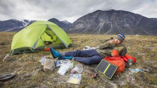 best solar charger: a camper powering up his tech with a solar charger