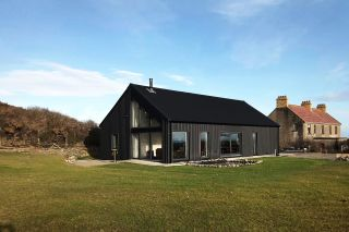 a black timber clad eco house in ardglass