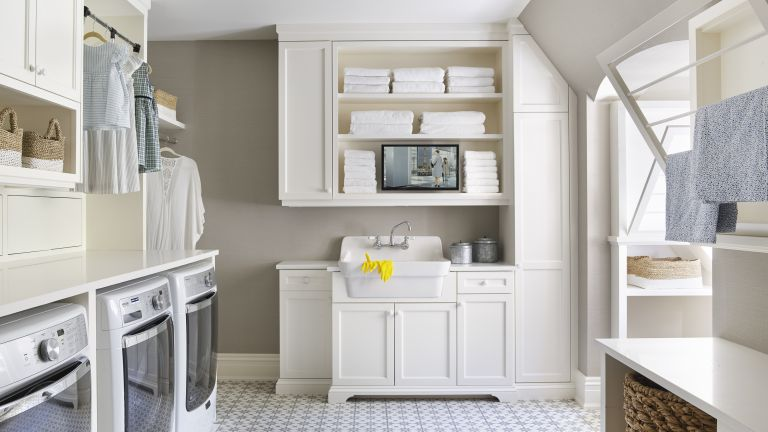 A white laundry room with tiled floors and clothes rail illustrating laundry room storage ideas