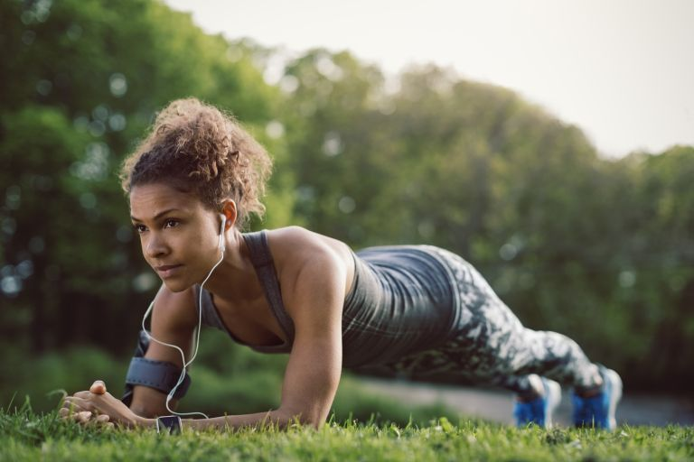 Young sporty woman doing a plank in the park