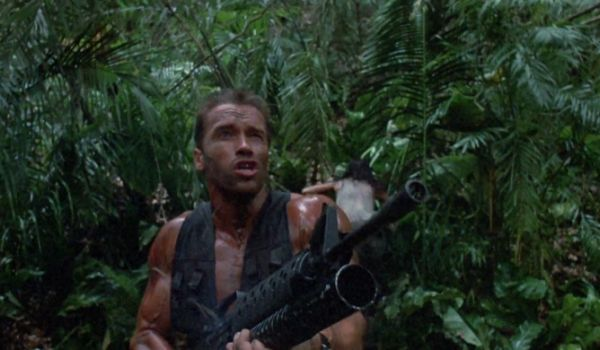 Arnold Schwarzenegger firing a big gun at the Predator
