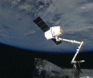 Dragon space capsule at the end of the International Space Station's robotic arm.