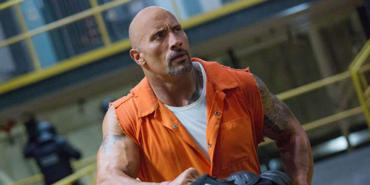 Luke Hobbs (Dwayne Johnson) wears a cut-off orange jumpsuit in prison in 'Hobbs and Shaw.'