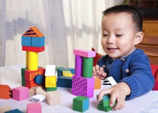 A preschooler plays with blocks