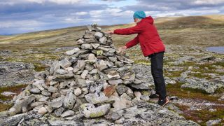 A hiker in a red jacket places rock on a rock cairn on a moor