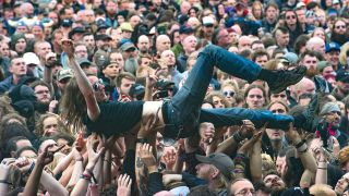 A photograph of an audience member crowdsurfing