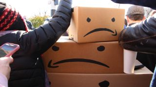 Amazon Protests outside potential headquarters HQ2 building in LIC New York. Photo shows altered versions of Amazon's logo, where instead of it smiling, it's angry.