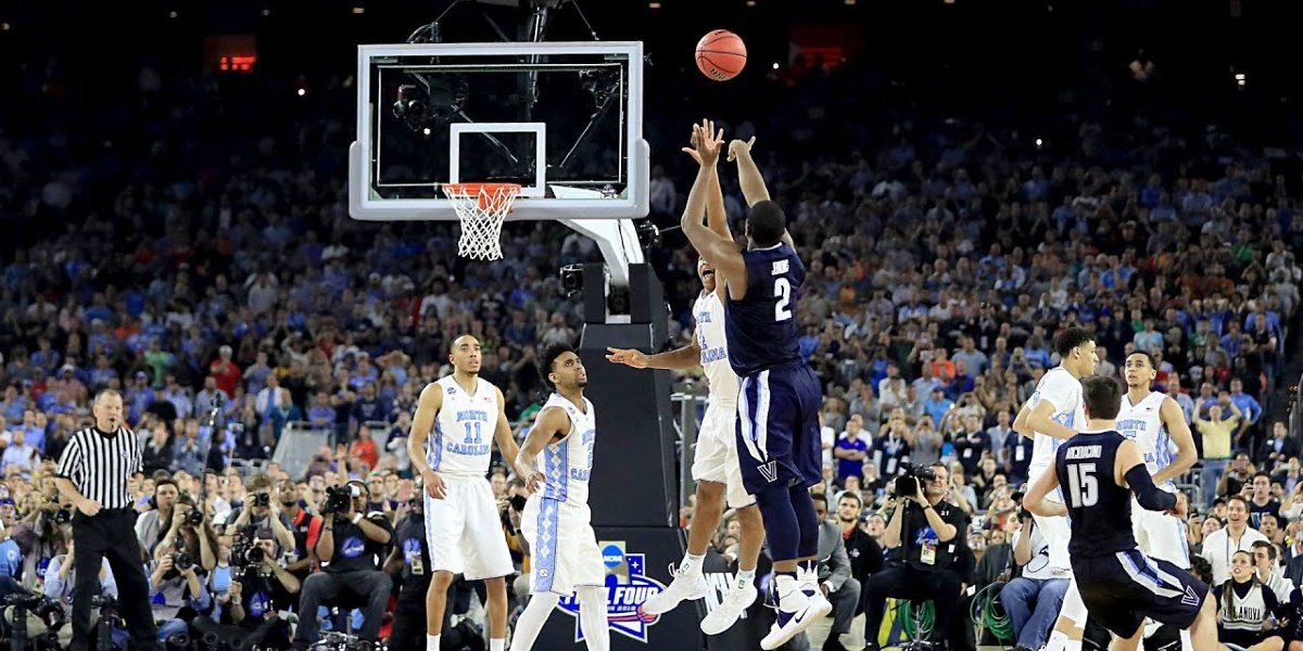 A college basketball player shots a 3-pointer at March Madness