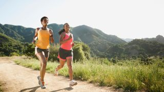 Women in shorts running on a trail