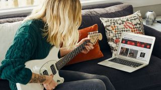 Guitarist with long blonde hair uses Fender Play to learn guitar remotely